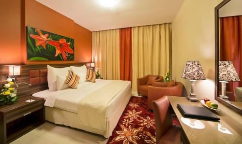 A bed or beds in a room at Abidos Hotel Apartment Dubai Land