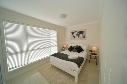 A bed or beds in a room at Craig's Place, 2br Short Term Accommodation - Western Sydney Area