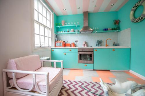 """A kitchen or kitchenette at Unique & fun coastal getaway, 1 minute walk to the beach - pastel interiors created by local artists in a Town centre location """"The Courtyard Suite"""""""