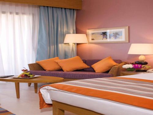 A bed or beds in a room at Mövenpick Resort & Spa Tala Bay Aqaba