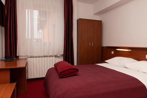 A bed or beds in a room at Hotel Mirni Kutak