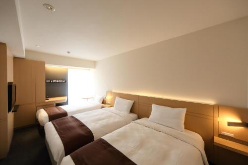 A bed or beds in a room at Hakata Tokyu REI Hotel