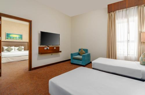 A bed or beds in a room at Ramada by Wyndham Dubai Deira