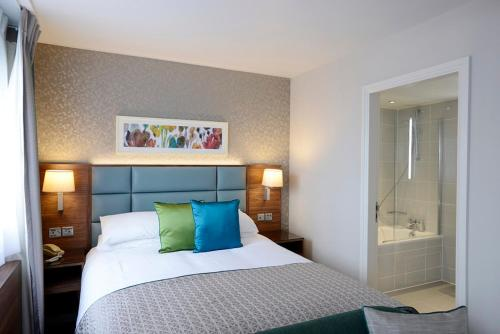 A bed or beds in a room at The Lensbury Resort