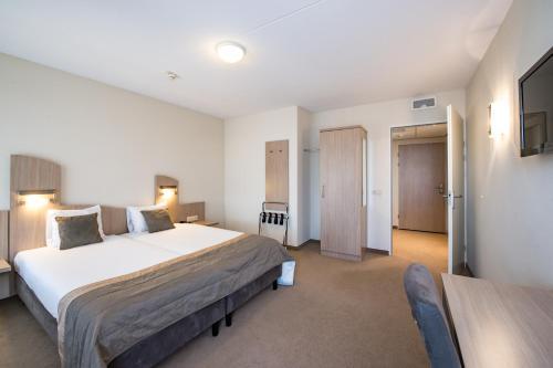 Een bed of bedden in een kamer bij Fletcher Wellness-Hotel Kamperduinen