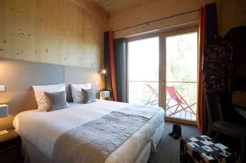 A bed or beds in a room at L'Aiguille Grive Chalets Hotel