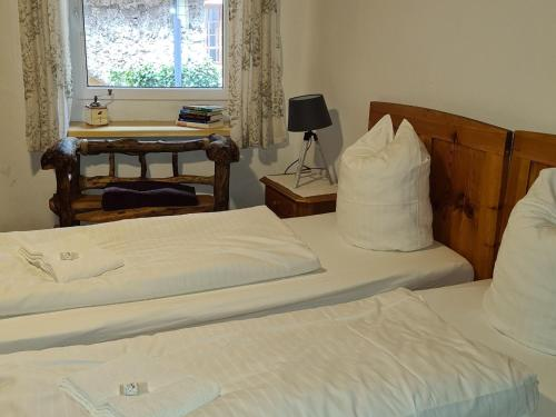 A bed or beds in a room at Pension Cafe zum Mühlbach