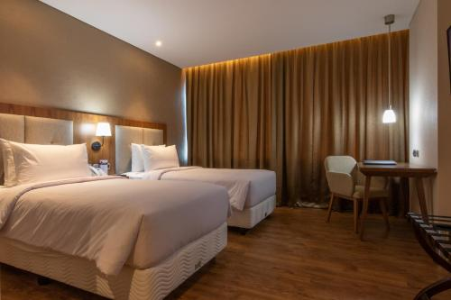 A bed or beds in a room at Avenzel Hotel & Convention Cibubur