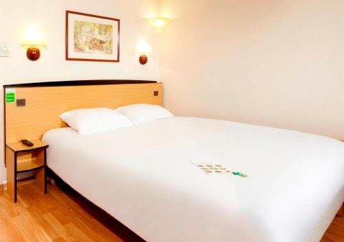A bed or beds in a room at Kyriad Direct Strasbourg Ouest - Zénith