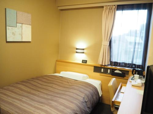 A bed or beds in a room at Hotel Route-Inn Shinagawa-Oimachi