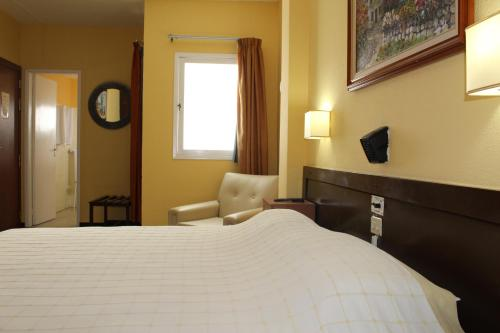 A bed or beds in a room at Hotel Olympia