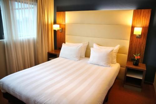 A bed or beds in a room at Van der Valk Hotel Rotterdam - Blijdorp