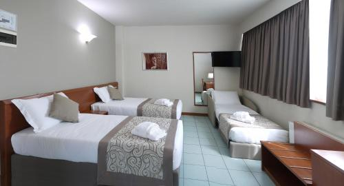 A bed or beds in a room at ALA Hotel