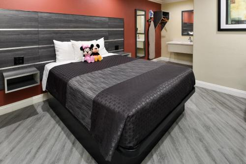 A bed or beds in a room at Pacific Inn Anaheim