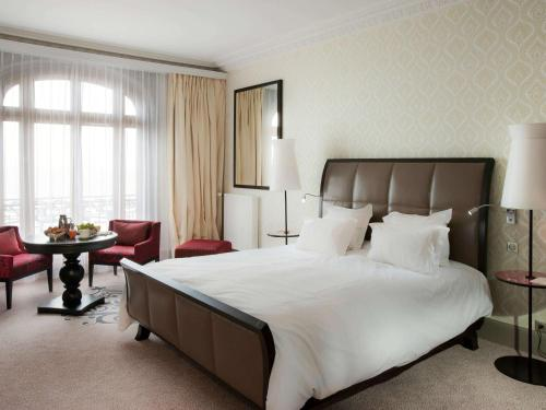 A bed or beds in a room at Le Grand Hotel de Cabourg - MGallery Hotel Collection