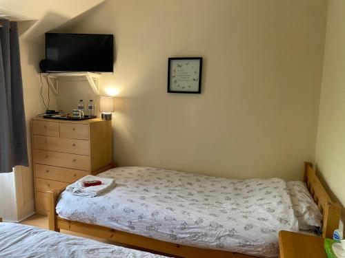 A bed or beds in a room at Aros Guest House