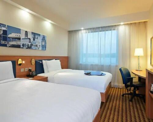 A bed or beds in a room at Hampton by Hilton Luton Airport