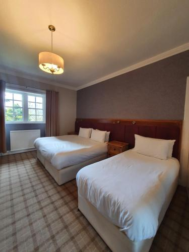 A bed or beds in a room at The Glen Hotel