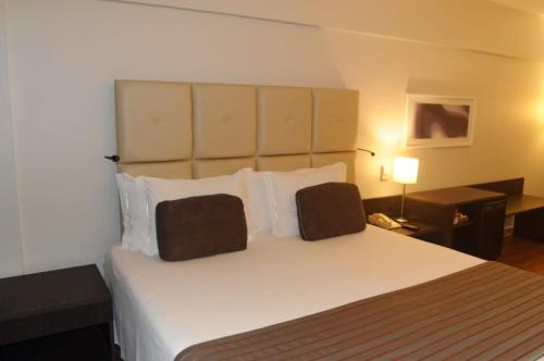 A bed or beds in a room at Sol Alphaville Hotel & Residence