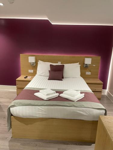 A bed or beds in a room at Holtwhites Hotel