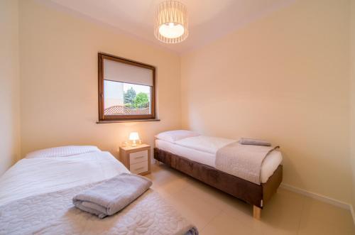 Łóżko lub łóżka w pokoju w obiekcie Gray House Apartamenty Dziwnówek
