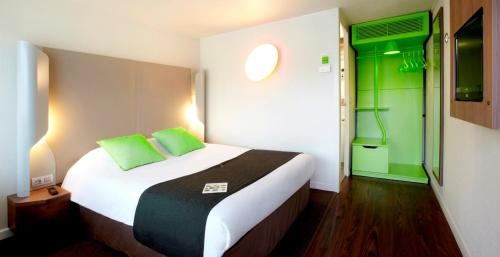 A bed or beds in a room at Campanile Biarritz