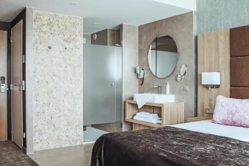 A bed or beds in a room at Van der Valk Hotel Princeville Breda