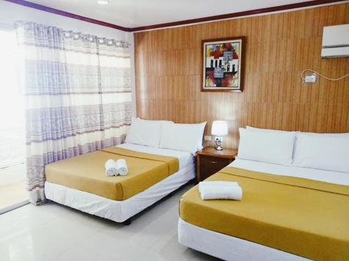 A bed or beds in a room at Shenna's Beach Resort