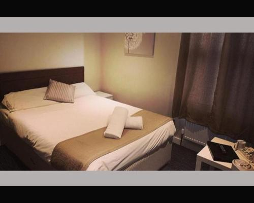 A bed or beds in a room at The R Inn Hotel