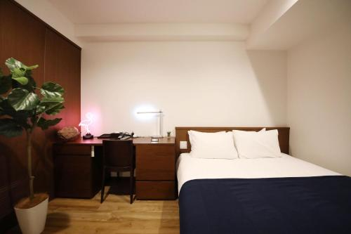 A bed or beds in a room at Toho Hotel Zonk Hakata