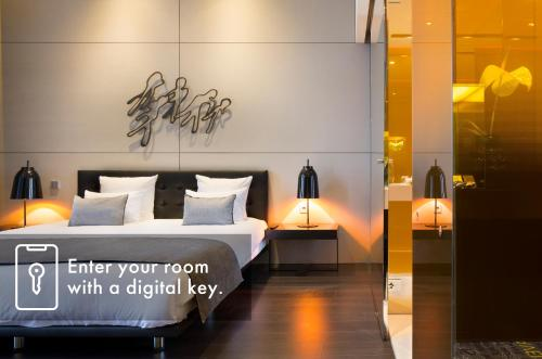 A bed or beds in a room at art'otel amsterdam, part of Radisson Hotel Group
