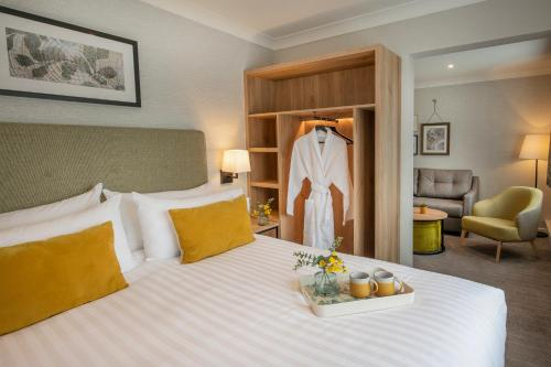 A bed or beds in a room at Horwood House Hotel