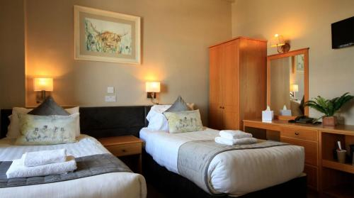 A bed or beds in a room at West Highland Hotel