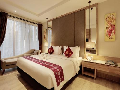 A bed or beds in a room at Bali Sunshine Inn Nusa Dua