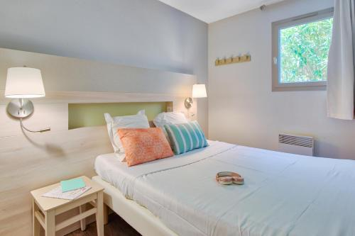 A bed or beds in a room at Résidence Pierre & Vacances Les Parcs de Grimaud