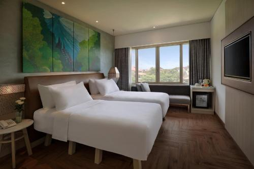 A bed or beds in a room at Mercure Kuta Bali