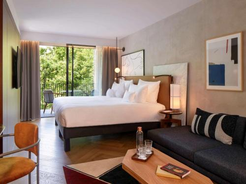 A bed or beds in a room at L'Esquisse Hotel & Spa Colmar - Mgallery