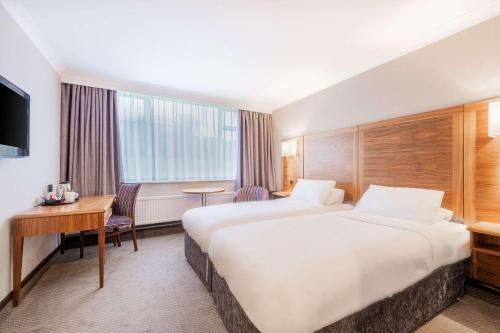 A bed or beds in a room at Clarion Cedar Court Huddersfield Hotel