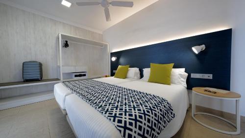 Een bed of bedden in een kamer bij Broncemar Beach Suites