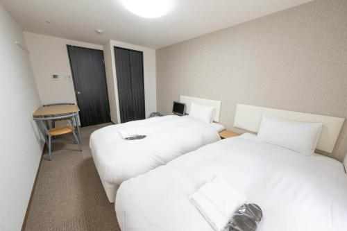 A bed or beds in a room at Stay Inn Kyoto Gojo