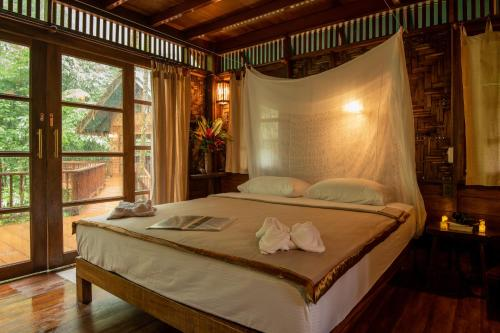 A bed or beds in a room at Our Jungle House - SHA Certified