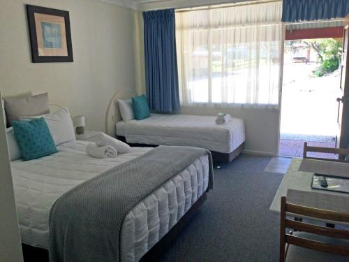 A bed or beds in a room at Alstonville Settlers Motel
