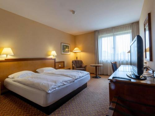 A bed or beds in a room at Mercure Hotel Gera City
