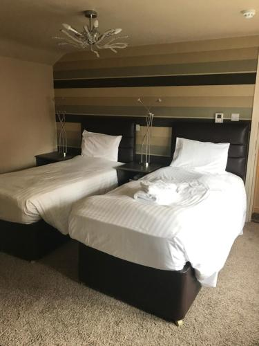 A bed or beds in a room at The White Swan