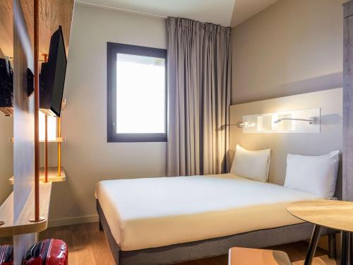 A bed or beds in a room at Ibis Budget Montpellier Aéroport Parc Des Expos