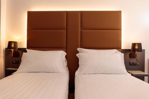 A bed or beds in a room at London Hotel