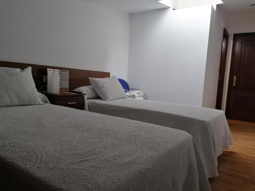 A bed or beds in a room at Pensión CHE
