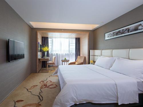 سرير أو أسرّة في غرفة في Vienna Hotel - Guangzhou South Railway Station Branch