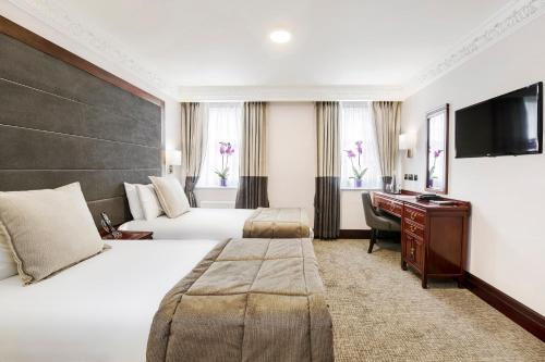 A bed or beds in a room at Fitzrovia Hotel