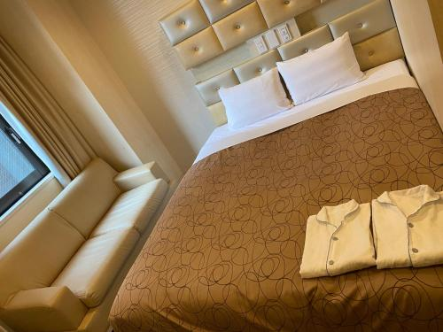 A bed or beds in a room at HOTEL RELIEF Sapporo Susukino